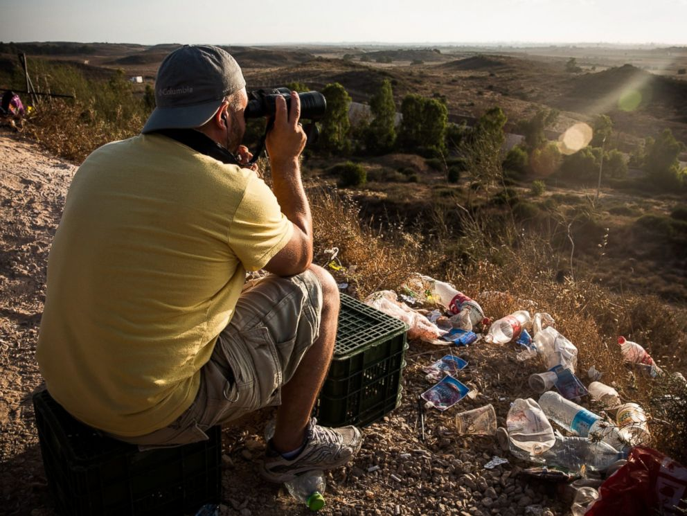 PHOTO: A man uses binoculars while waiting to watch Israeli attacks inside Gaza from the top of a hill on the sixth day of Israels operation Protective Edge on July 13, 2014 in Sderot, Israel.