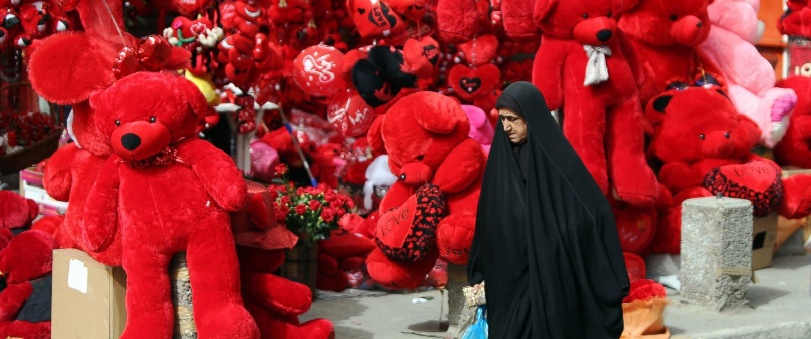 PHOTO: An Iraqi woman walks past a shop displaying red teddy bears in preparation for Valentines day in Baghdads Karrada district, Feb. 12, 2015.