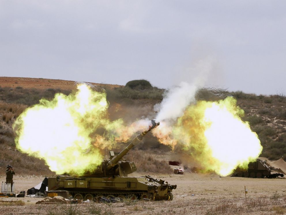 PHOTO: An Israeli army self-propelled howitzer cannon fires a shell from the Israel-Gaza border