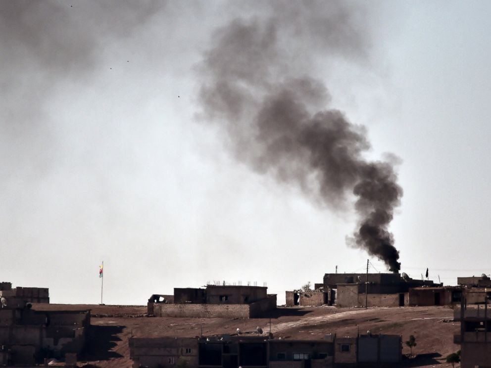 PHOTO: Smoke rises from the central part of the Syrian town of Ain al-Arab, known as Kobani by the Kurds, as seen from the Turkish-Syrian border, as a Kurdish flag waves during heavy fighting, in the southeastern town of Suruc, Turkey, Oct. 7, 2014.