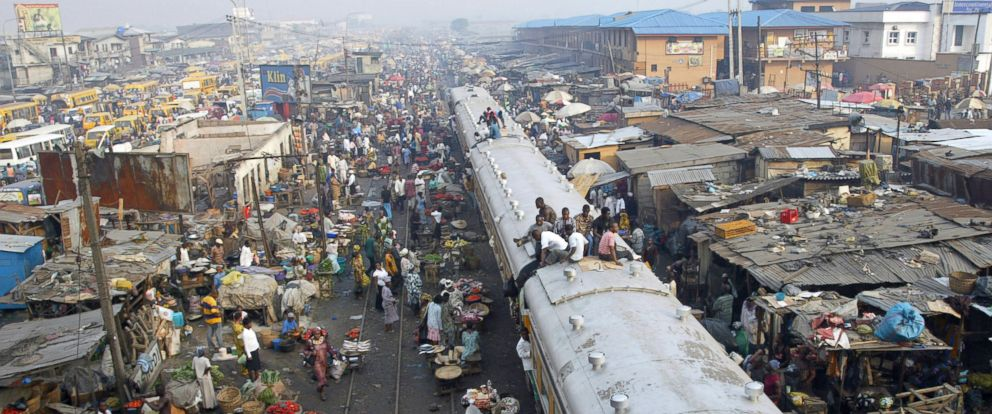 PHOTO: Commuters sit on top of a train chasing away vendors hawking their wares on the rail track at Oshodi district of Lagos, November 2007.