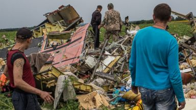 PHOTO: A group of people are pictured looking at the wreckage of Malaysia Airlines Flight 17 on July 18, 2014 in Grabovka, Ukraine.
