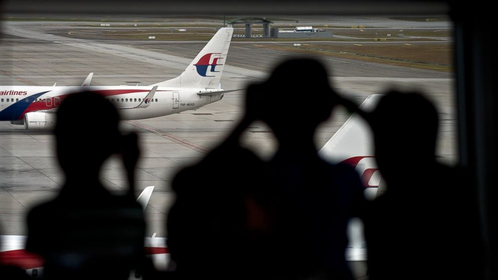 PHOTO: Malaysian children are silhouetted as they watch a Malaysia Airlines plane taxi on the runway at Kuala Lumpur International Airport in Sepang, March 17, 2014.