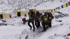 PHOTO: An injured person is carried by rescue members to be airlifted by rescue helicopter at Everest Base Camp on April 26, 2015, a day after an avalanche triggered by an earthquake devastated the camp.