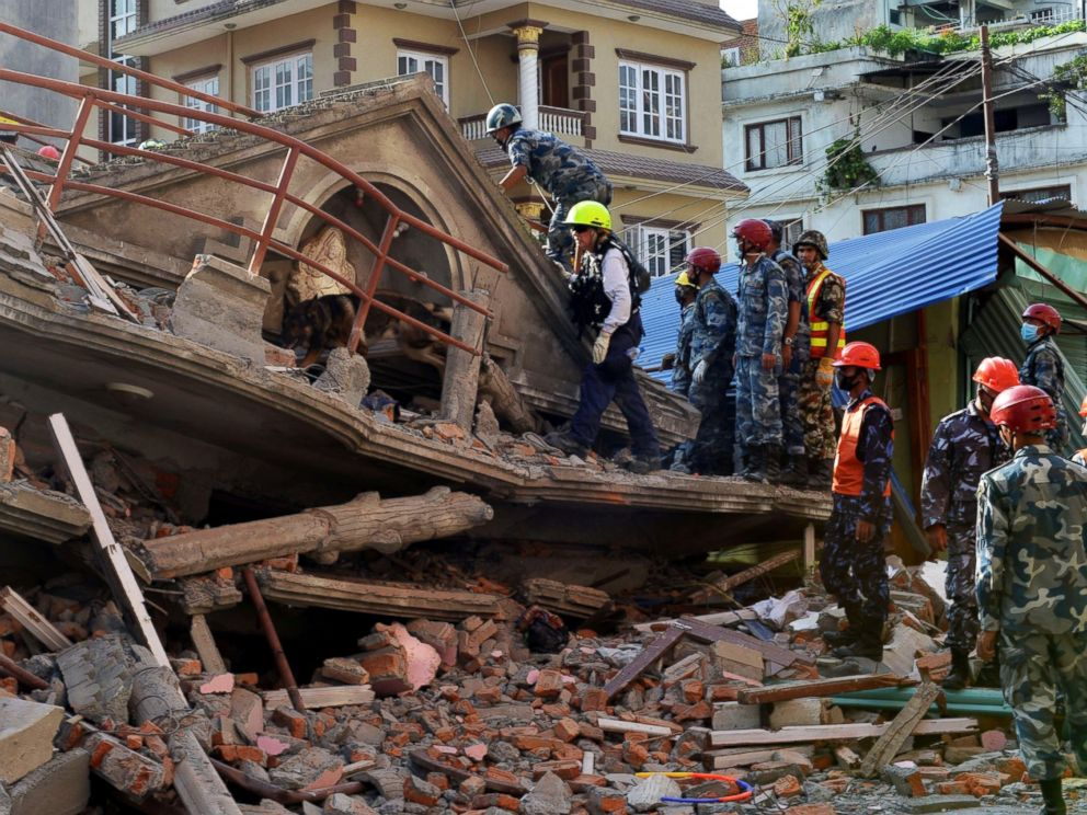 PHOTO: U.S. rescue team officials with a sniffer dog search for survivors at a collapsed house in Kathmandu on May 12, 2015, after an earthquake struck.