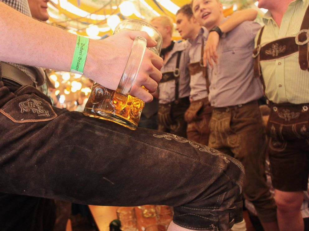 PHOTO: Revellers dressed with traditional Bavarian Lederhosen trousers enjoy drinking beer