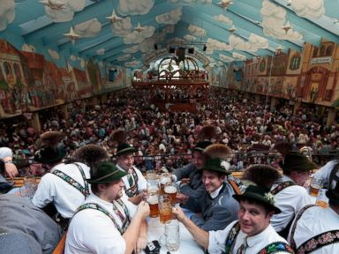 PHOTO: Visitors wearing traditional Bavarian clothes clink beer glasses in the Hacker-Pschorr tent