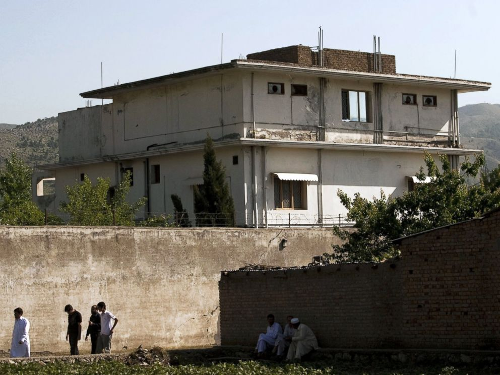 PHOTO: People walk past Osama Bin Ladens compound, May 3, 2011, in Abottabad, Pakistan.