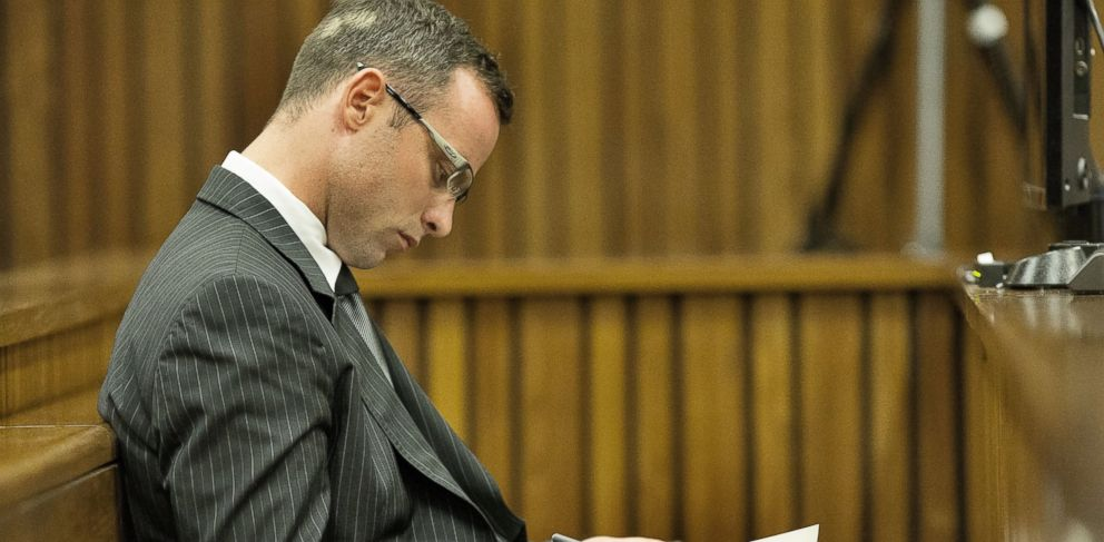 PHOTO :Oscar Pistorius spent part of his time in court during his murder trial underlining passages in a religious book or fingering rosary beads.