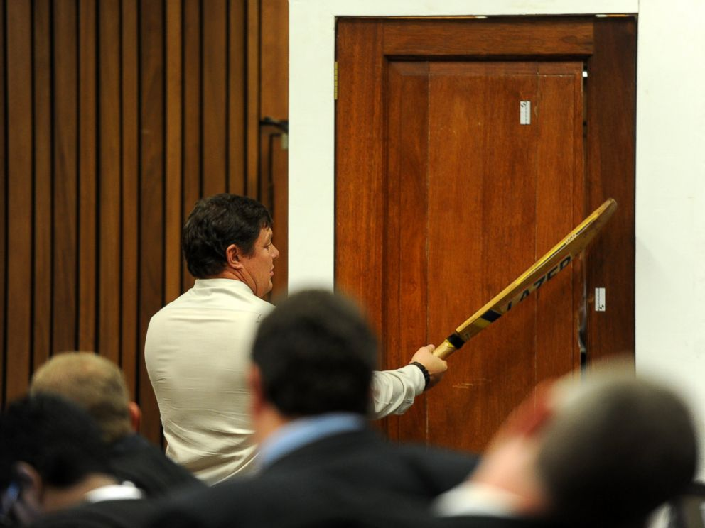 PHOTO: Forensic investigator Johannes Vermeulen takes part in the reconstruction of hitting a door with a cricket bat during the trial of Oscar Pistorius in Pretoria, South Africa on March 12, 2014.