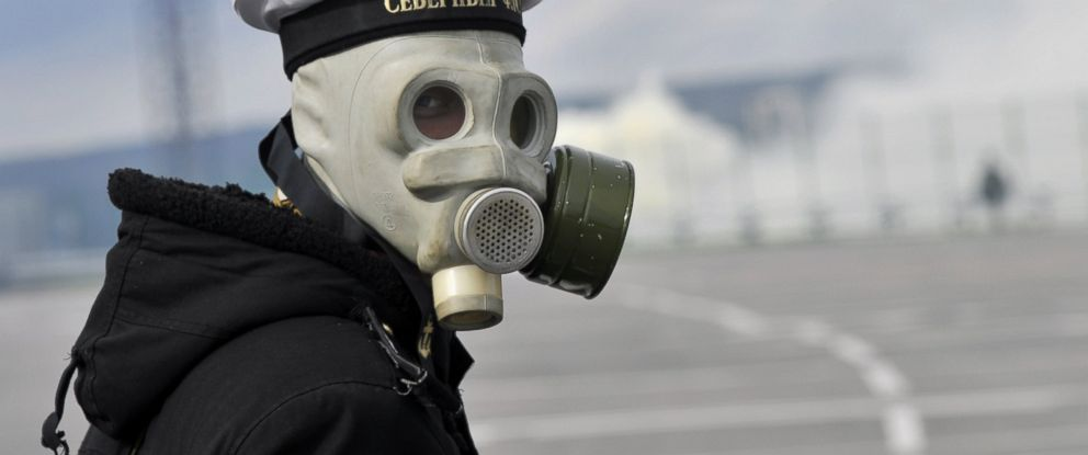 PHOTO: A serviceman of a radiological, chemical and biological defense unit wearing a gas mask takes part in a military drill to create smoke screens to conceal the Russian Northern Fleet base in Severomorsk.