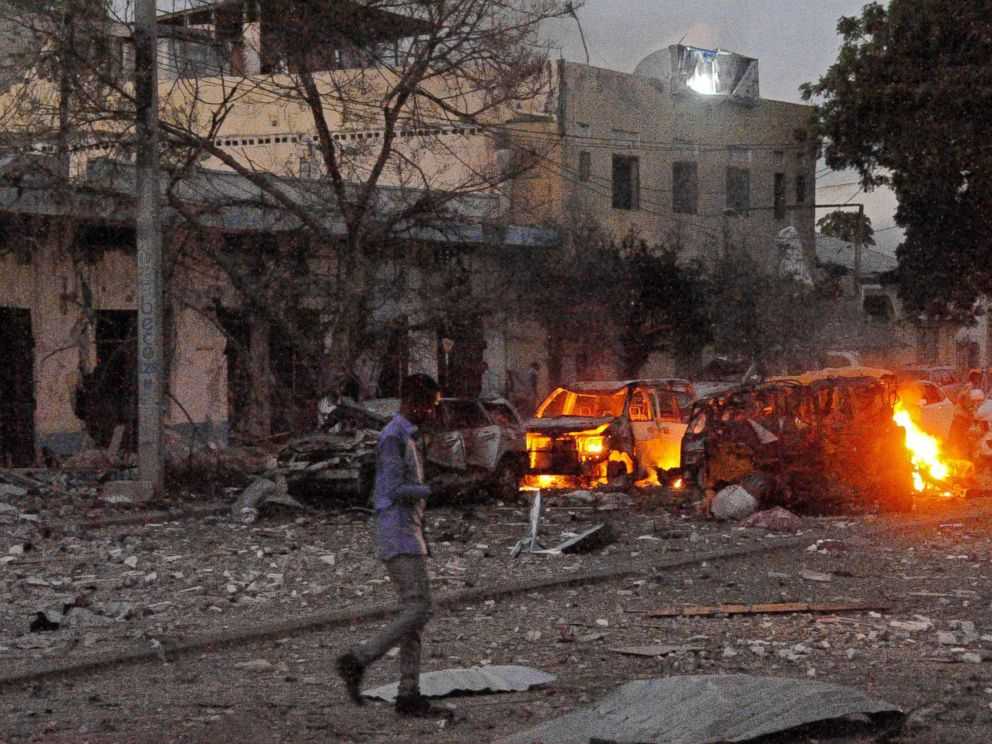 PHOTO: A man walks past the scene after a car bomb exploded, June 1, 2016, outside a Mogadishu hotel that houses several MPs, killing several people, and followed by a gun battle.