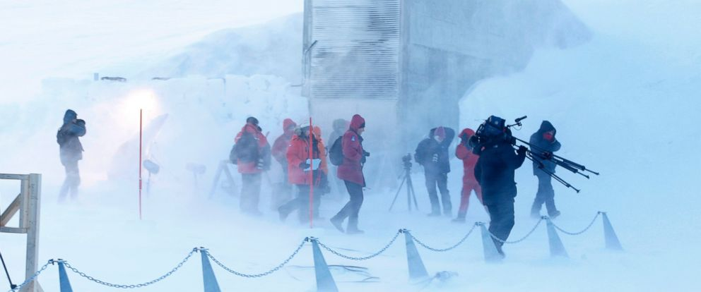 PHOTO: Journalists and cameramen walk under a gust of cold wind near the entrance of the Svalbard Global Seed Vault that was officially opened near Longyearbyen, Norway in this Feb. 26, 2008 file photo.