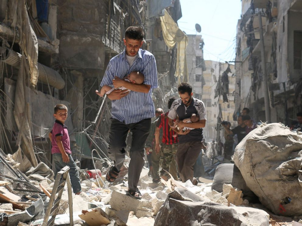 PHOTO: Syrian men carrying babies make their way through the rubble of destroyed buildings following a reported air strike on the rebel-held Salihin neighborhood of the northern city of Aleppo, Sept. 11, 2016.