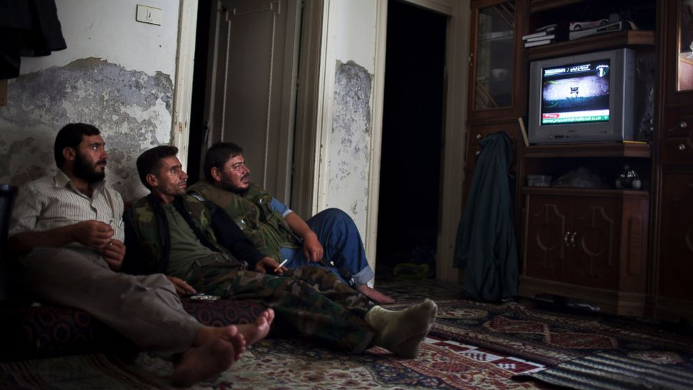 PHOTO: Syrian opposition fighters watch television