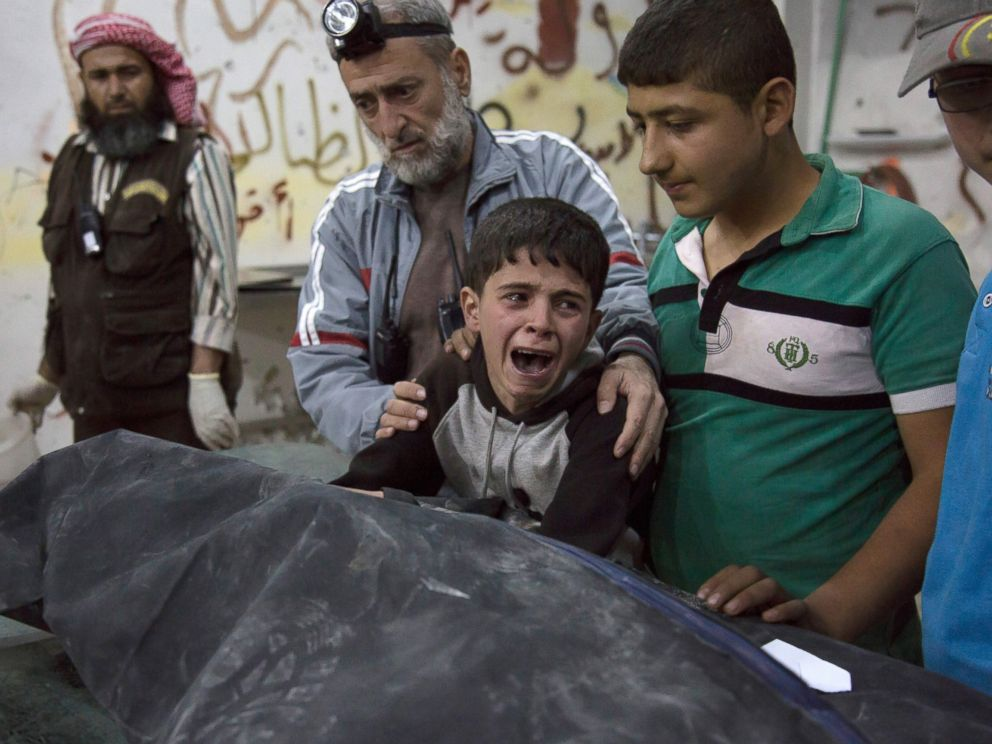 PHOTO: A Syrian boy is comforted as he cries next to the body of a relative who died in a reported airstrike on April 27, 2016 in the rebel-held neighborhood of al-Soukour in the northern city of Aleppo.