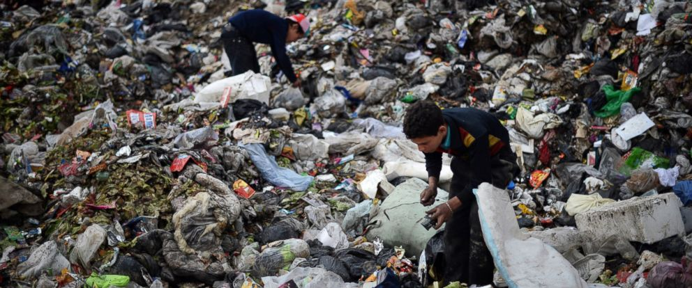 PHOTO: Young Syrian boys collect plastic and metal items in a garbage dump in the northern Syrian city of Aleppo on April 17, 2013.