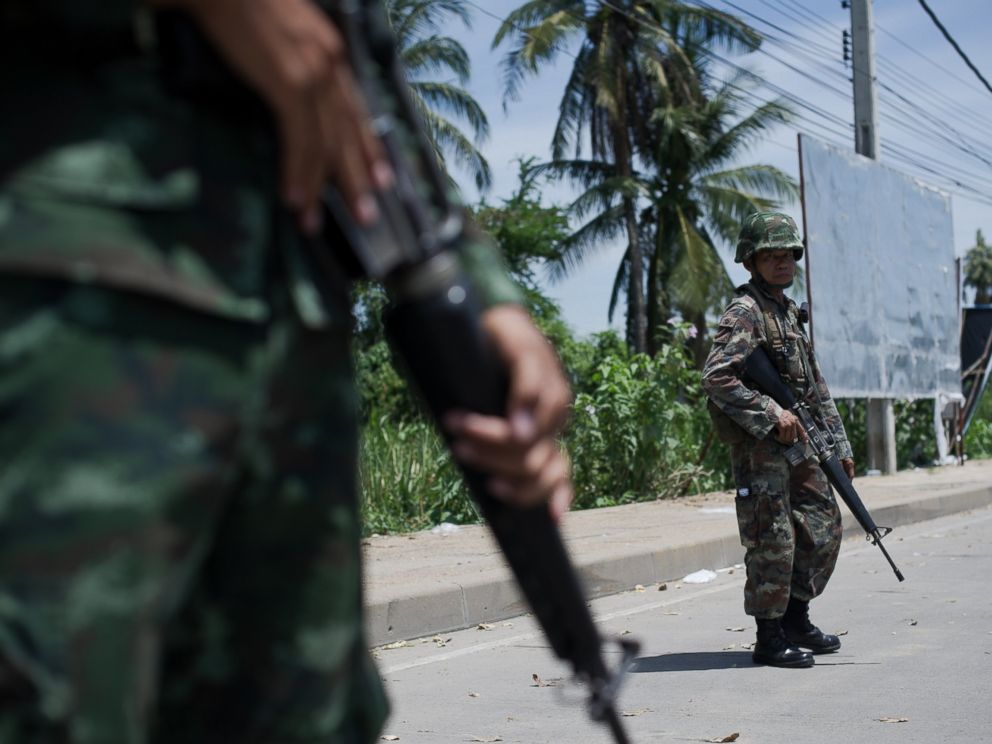 PHOTO: Thai army soldiers stand at a checkpoint near where pro-government Red shirts have been rallying for days on the outskirts of Bangkok on May 20, 2014.