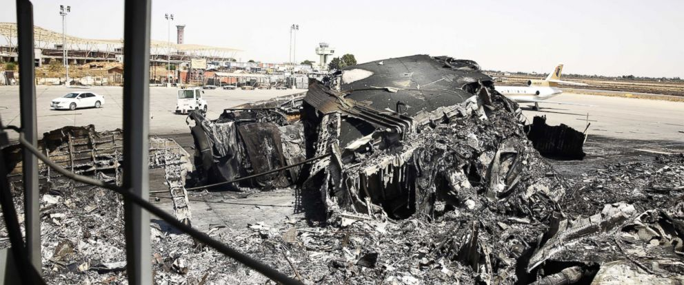 PHOTO: A burnt airplane lies at Tripoli international airport in the Libyan capital on July 21, 2014, after militias stepped up their assault on the countrys main airport.