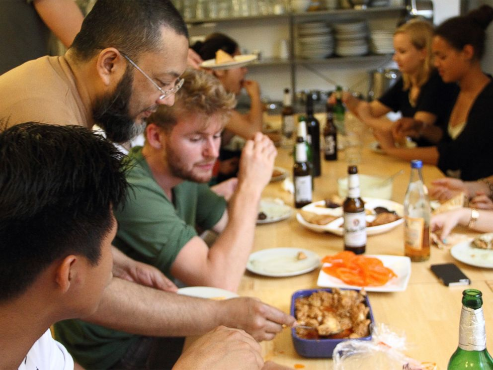 PHOTO: Refugees and Germans sharing a meal at a community kitchen event organized by Ueber den Tellerrand kochen -