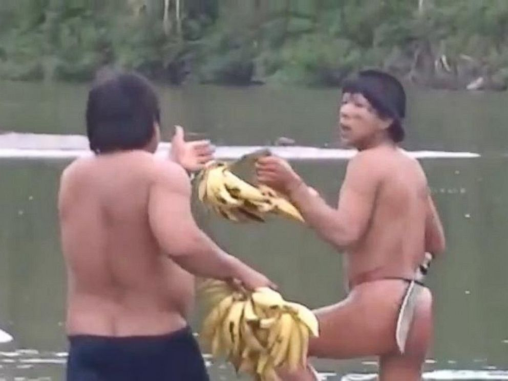 PHOTO: An Ashaninkan man, left, gives members of the uncontacted tribe, right, some fruit in this frame grab from an undated video taken on the banks of the Envira River in Brazil.