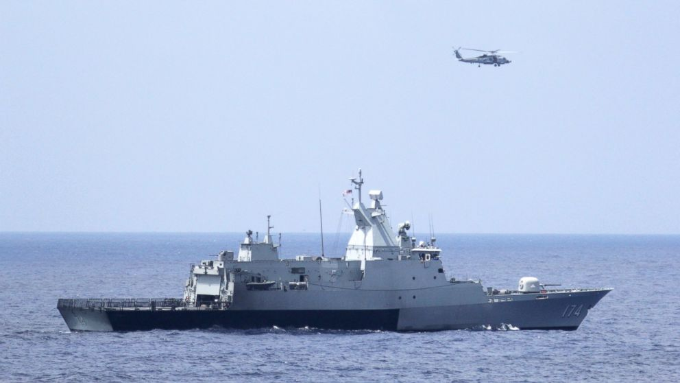 PHOTO: A Malaysian naval ship is flanked by a U.S Navy Sea Hawk helicopter in the search for missing flight MH370 from Malaysia.