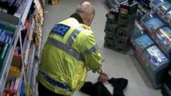 PHOTO: Surveillance video shows police tasering a knife-wielding man as he tried to rob a British supermarket.