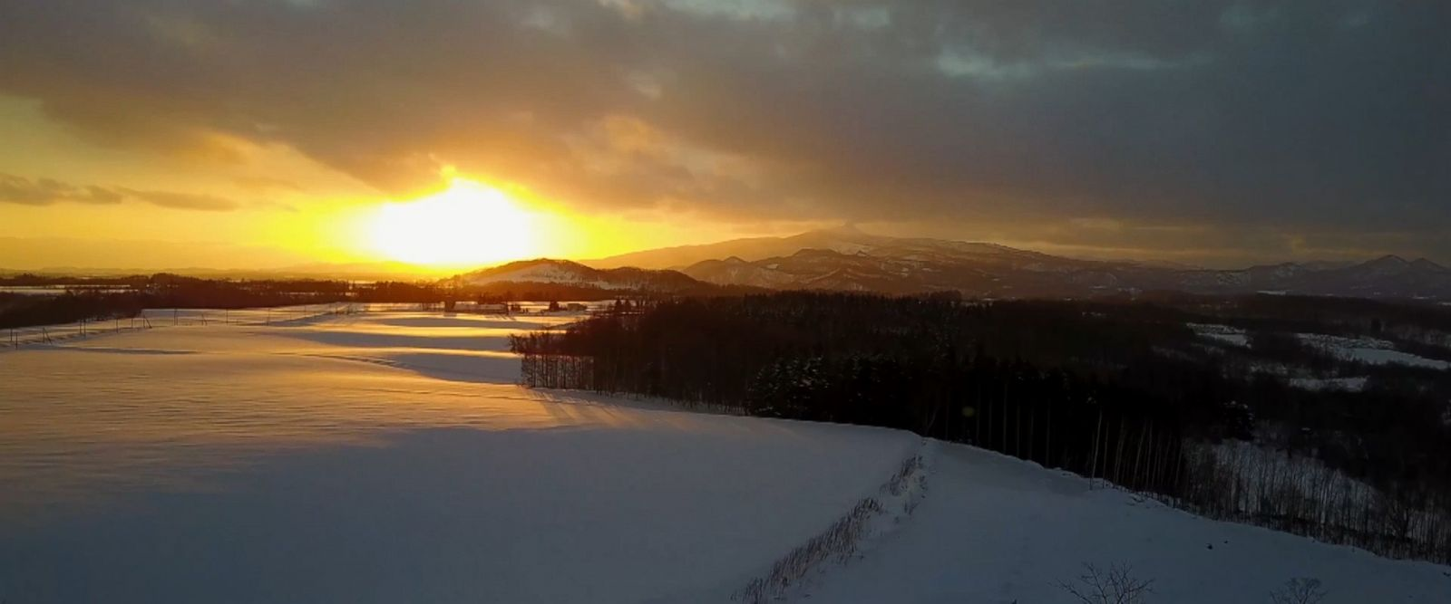 Drone captures breathtaking footage of the sun setting over a stunning snowy landscape in Hokkaido, Japan.