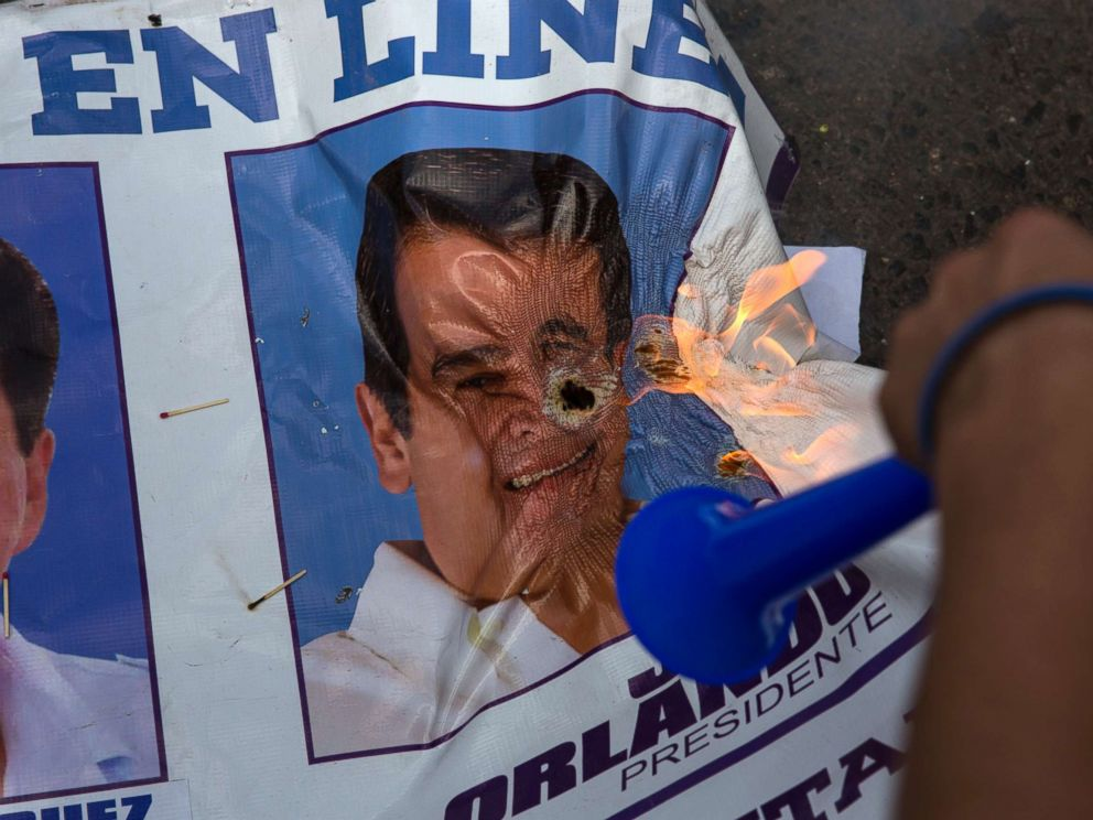 PHOTO: A banner promoting Honduran President Juan Orlando Hernandez burns after being set on fire by supporters of challenger Salvador Nasralla, during a protest march claiming electoral fraud, in Tegucigalpa, Honduras, Nov. 29, 2017.