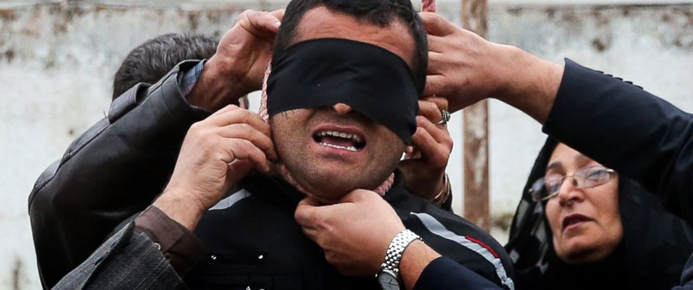 PHOTO: The mother, right, of Abdolah Hosseinzadeh, who was murdered in 2007, removes the noose with the help of her husband from around the neck of Balal, who killed her son, during the execution ceremony in Nowshahr, April 15, 2014.