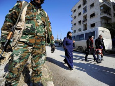PHOTO: People that came back to inspect their homes walk near government soldiers in government controlled Hanono housing district in Aleppo, Syria, Dec. 4, 2016.