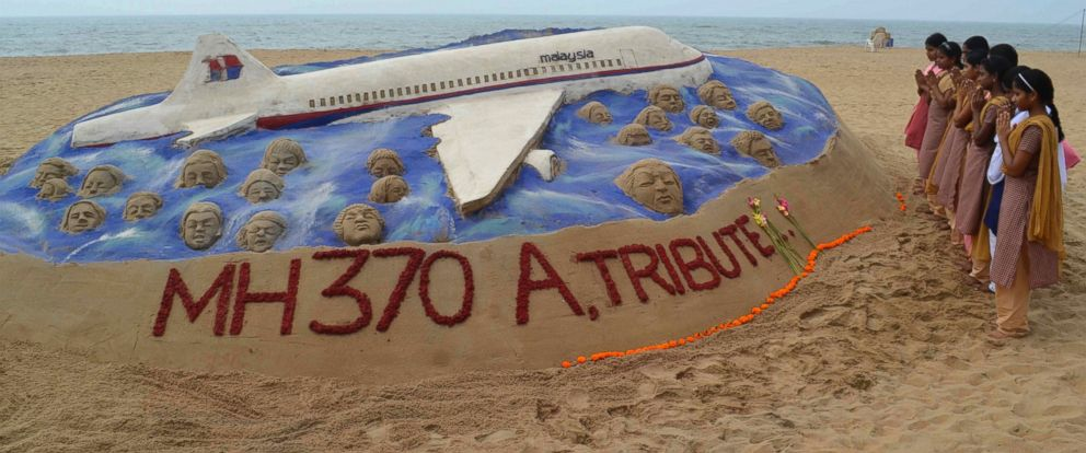 PHOTO: Schoolgirls pray next to a sand art sculpture created by Indian sand artist Sudarshan Patnaik to pay tribute to the passengers and crew onboard the missing Malaysia Airlines flight MH370.