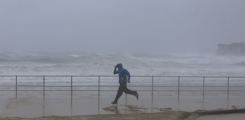 PHOTO: A man runs past heavy seas as sand is blown inland by heavy winds at Sydneys Bondi Beach