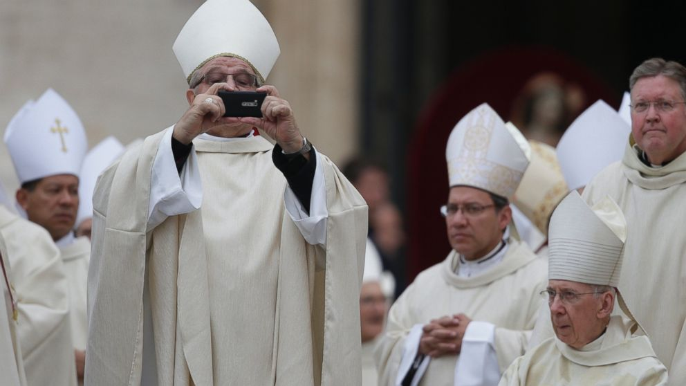 PHOTO: A bishop uses his mobile phone to take photographs as he arrives for the canonization ceremony of Popes John XXIII and John Paul II to start in St. Peters Square at the Vatican April 27, 2014.