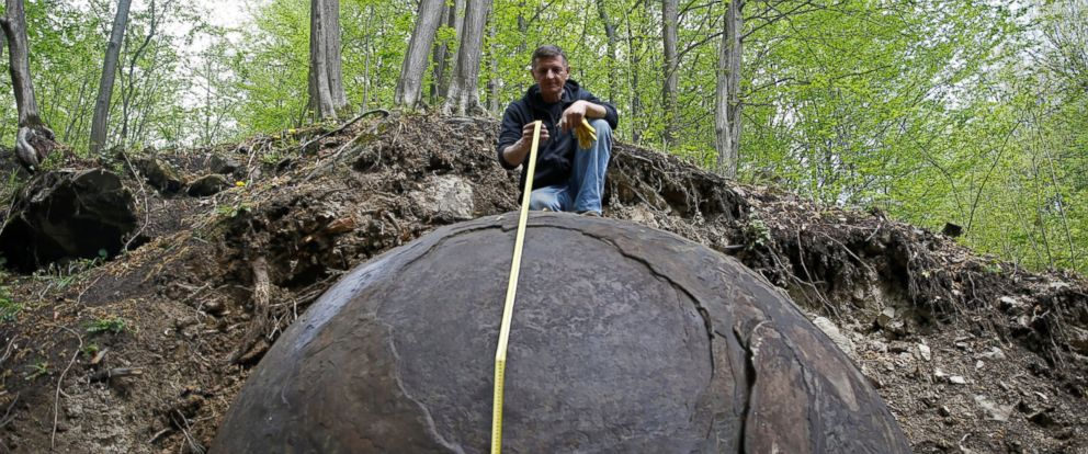 PHOTO: Suad Keserovic poses as he measures a stone ball in Podubravlje village near Zavidovici, Bosnia and Herzegovina, April 11, 2016.