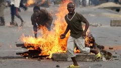 PHOTO: A protester runs in front of a burning barricade during a protest against Burundi President Pierre Nkurunziza and his bid for a third term in Bujumbura, Burundi, May 21, 2015.