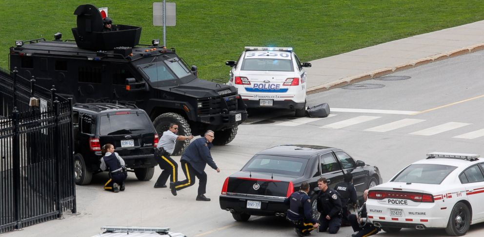 PHOTO: Police officers take cover near Parliament Hilll following a shooting incident in Ottawa, Oct. 22, 2014.