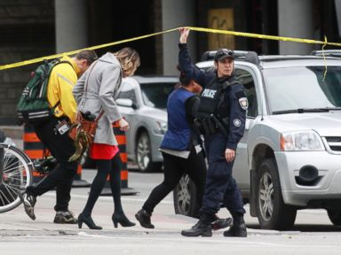 PHOTO: An Ottawa police officer holds up a length of police tape for pedestrians leaving the downtown area following shooting incidents in Ottawa, Oct. 22, 2014.