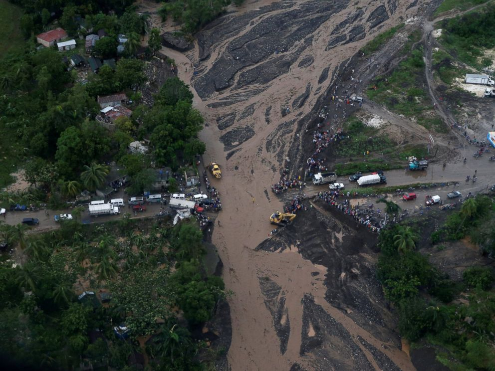 PHOTO: People gather next to a collapsed bridge after Hurricane Matthew passes Petit Goave, Haiti, Oct. 5, 2016.