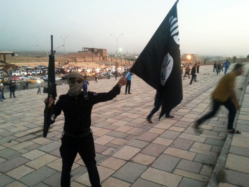 PHOTO: A fighter of the Islamic State of Iraq and the Levant (ISIL) holds an ISIL flag and a weapon on a street in the city of Mosul, June 23, 2014.