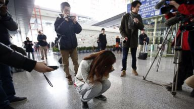 PHOTO: Journalists attempt to interview a woman who is the relative of a passenger on Malaysia Airlines flight MH370, as she crouches on the floor crying, at the Beijing Capital International Airport in Beijing, March 8, 2014.