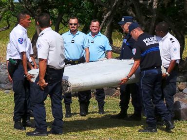 PHOTO: French gendarmes and police carry a large piece of plane debris which was found on the beach in Saint-Andre, on the French Indian Ocean island of La Reunion, July 29, 2015.