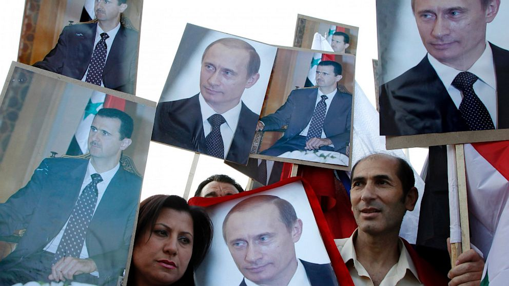 PHOTO: Supporters of Syrian President Bashar al-Assad hold signs with images of al-Assad and Russian President Vladimir Putin after Putin was sworn in as president, in front of the Russian embassy in Damascus May 7, 2012.