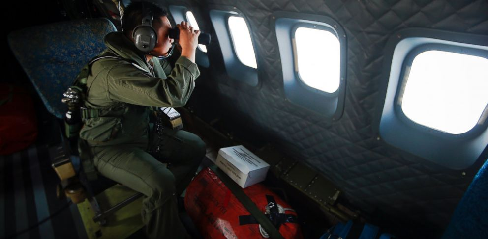 PHOTO: A crew member from the Royal Malaysian Air Force uses binoculars onboard a Malaysian Air Force CN235 aircraft during a Search and Rescue (SAR) operation to find the missing Malaysia Airlines flight MH370, in the Straits of Malacca March 13, 2014.