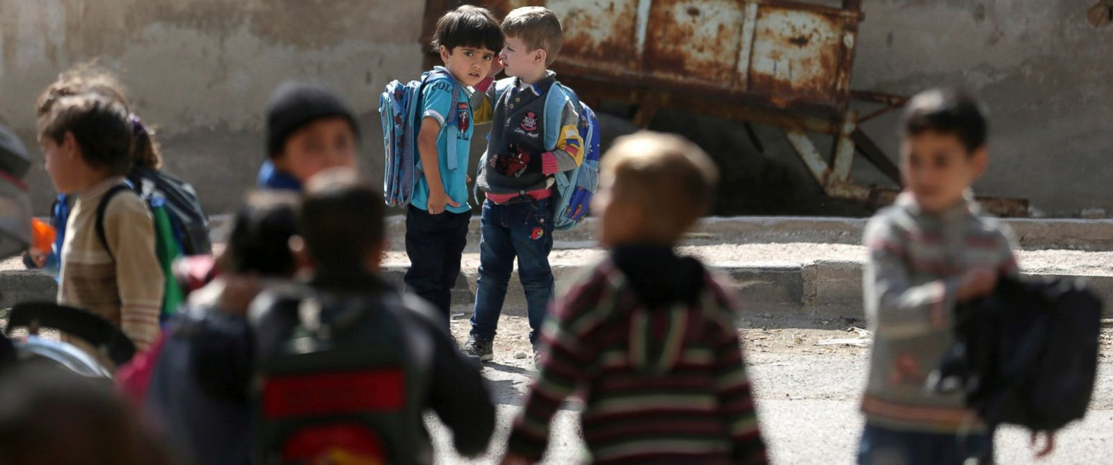 PHOTO: Children carrying school bags stand near the Nabaa Al-Hayat center for education and psychosocial support for children in places undergoing a crisis, in eastern al-Ghouta, near Damascus, Oct. 21, 2014.