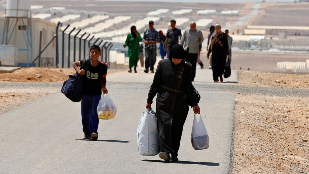 PHOTO: Newly-arrived Syrian refugees carry their belongings as they walk at Azraq refugee camp near Al Azraq area, east of Amman, Jordan, Aug. 19, 2014.