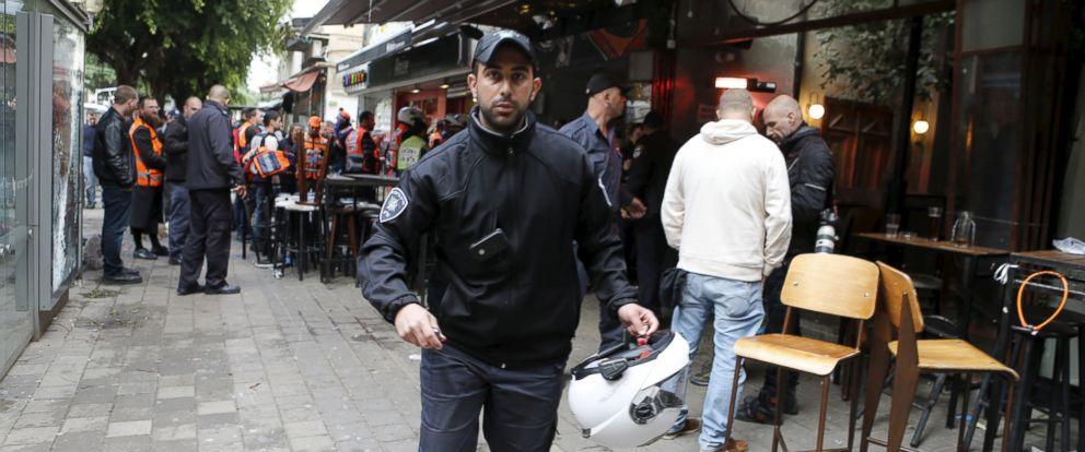 PHOTO: Israeli policemen runs at the scene of a shooting incident in Tel Aviv, Jan. 1, 2016.