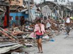 PHOTO: Residents cover their noses as they walk past devastated houses after super typhoon Haiyan hit Tacloban city, central Philippines, Nov. 11, 2013.