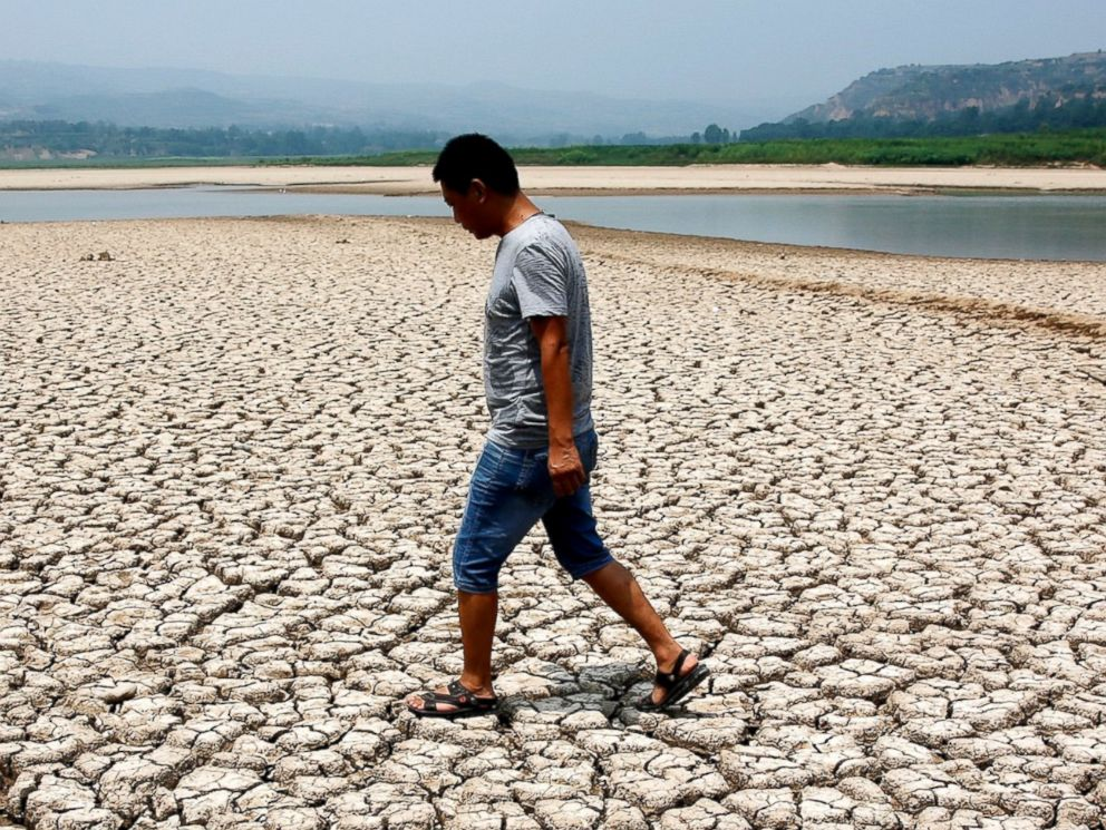 PHOTO: A man walks through the dried-up bed of a reservoir in Sanyuan county, Shaanxi, China, July 30, 2014.