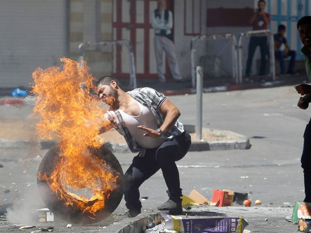 PHOTO: A man pushes a burning tire during a protest against the Israeli offensive in the West Bank City of Hebron, Gaza, Aug. 22, 2014.